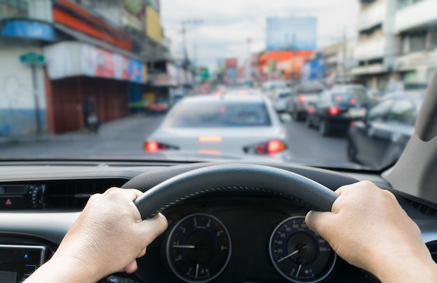 Handen die sturende auto in de opstopping houden