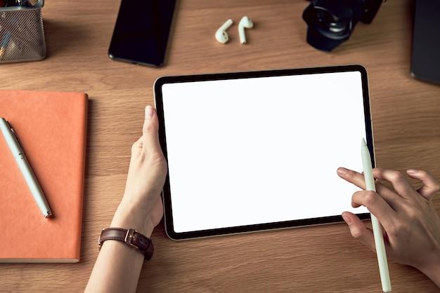 Handen die tablet met het lege scherm gebruiken en digitale pen houden