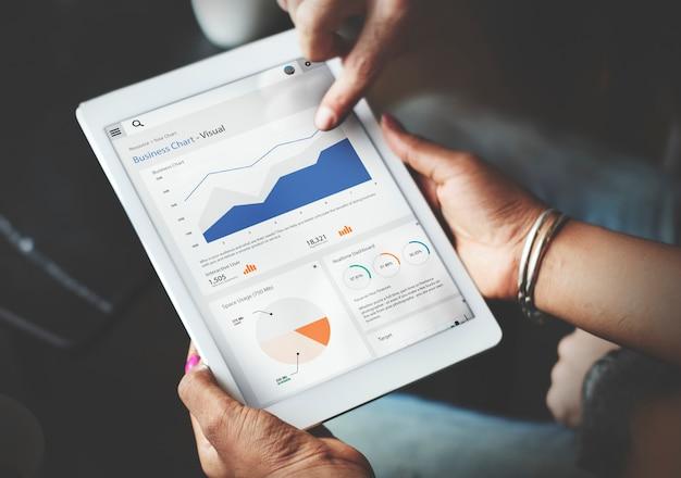 Handen die tabletscherm gebruiken die statistieken bedrijfsgegevens tonen