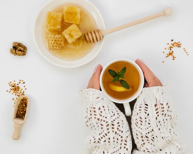 Handen die thee met honing houden