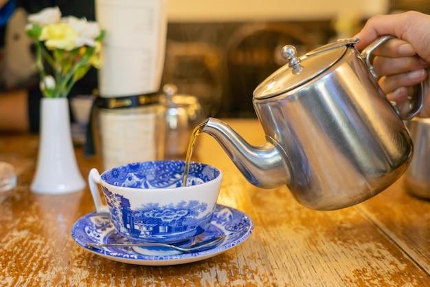 Handen die thee van een theepot gieten in een kop