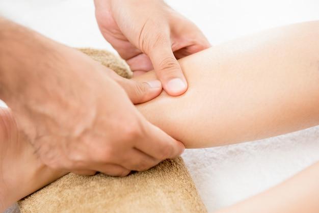 Handen die van mannelijke therapeut massage geven aan een vrouwenbeen