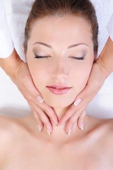 Handen die van schoonheidsspecialiste de mooie massage van het vrouwengezicht geven
