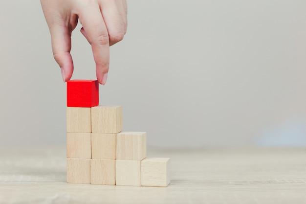 Handen die van zaken, houten blokken stapelen.