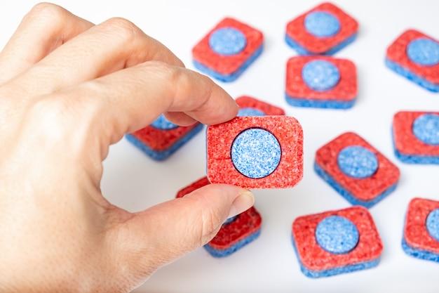Handen die vele rode en blauwe tabletten van de afwasmachinezeep dicht tegenhouden, witte achtergrond