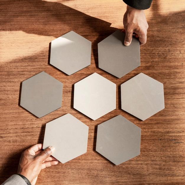 Handen die verbonden zeshoek uitgesneden papieren regelen