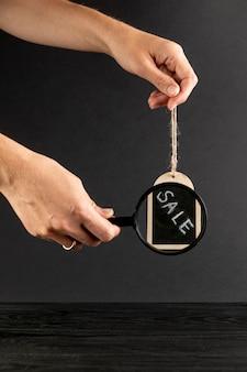 Handen die vergrootglas op verkoopadvertentie gebruiken