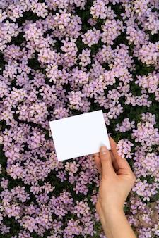 Handen die verticale kaart met bloemen houden