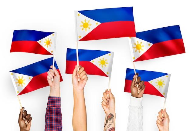 Handen die vlaggen van de filippijnen golven