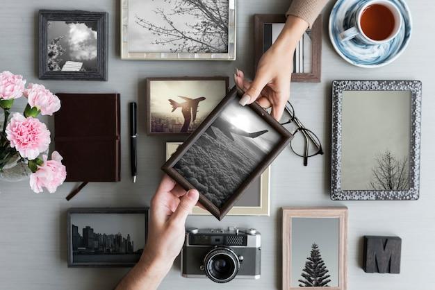 Handen die voor een fotokader over een fotolijstcollage bereiken