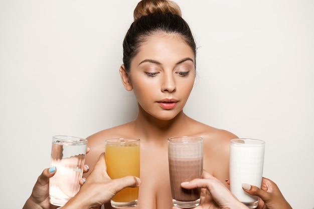 Handen die water, sap, koffie of melk aanbieden aan mooie vrouw