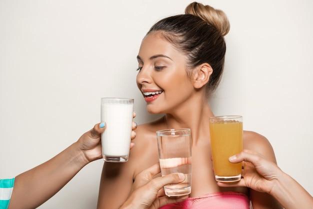 Handen die water, sap of melk aanbieden aan mooie vrouw