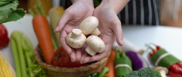 Handen die witte champignonpaddestoelen houden terwijl status bij lijst met andere verse landbouwbedrijfgroenten