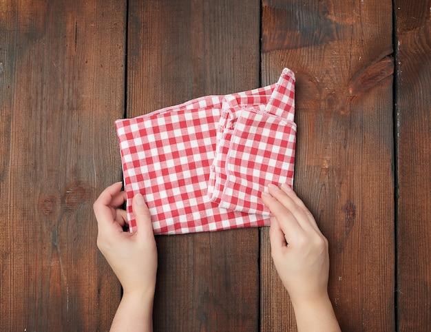 Handen die witte en rode geruite keukenhanddoek houden