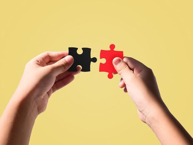 Handen die zwarte en rode kleurenpuzzels houden die op mooie pastelkleur worden geïsoleerd.