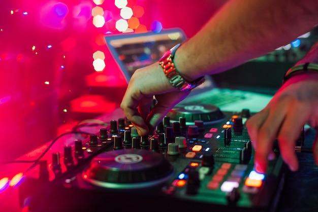 Handen dj mixen en afspelen van muziek op een professionele controller mixer