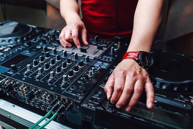 Handen dj mixen van muziek in de club tijdens het evenement