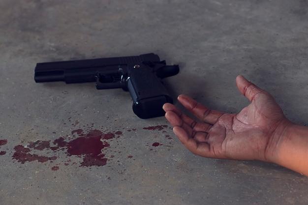 Handen doordrenkt met bloed en pistool op de vloer