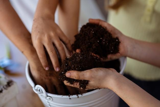 Handen en aarde. close-up van kinderen en leraar die potgrond vasthoudt tijdens de les ecologie op school
