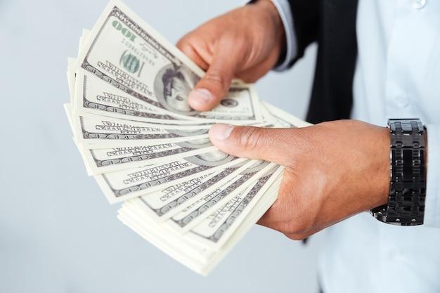 Handen en afrikaanse jonge man die geld aanhoudt