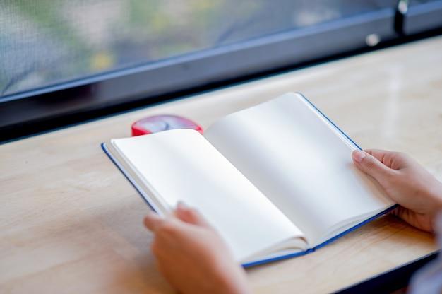 Handen en boeken die ontbloot zijn van ruimte in de ochtendkamer