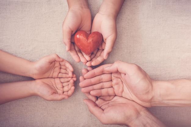 Handen en rood hart, ziekteverzekering, schenking en liefdadigheidsconcept