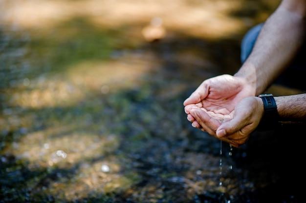 Handen en water stroomt uit natuurlijke watervallen waterconcept van natuurlijke waterval