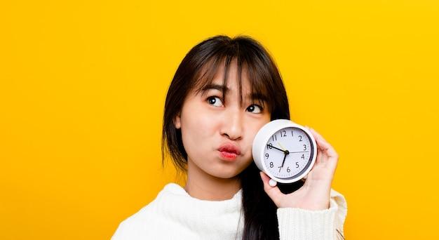 Handen en wekker van een mooie en schattige aziatische vrouw die vrolijk lacht het concept van tijd bekijken en tijd hebben