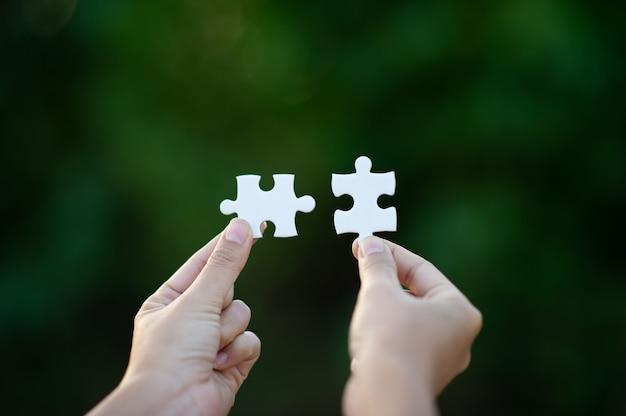 Handen en witte puzzelstukken
