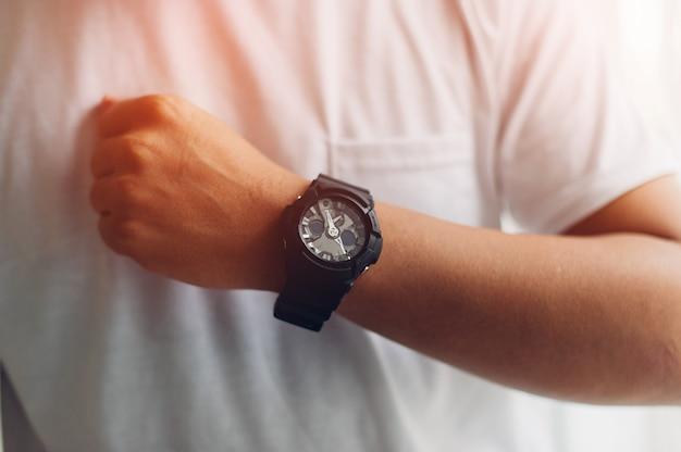 Handen en zwarte horloges van jonge mannen die van horloges met tijdconcept houden
