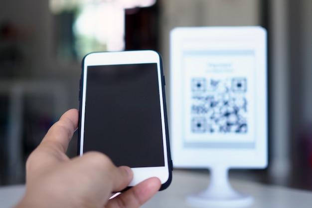 Handen gebruiken de telefoon om qr-codes te scannen om kortingen op aankopen te ontvangen.