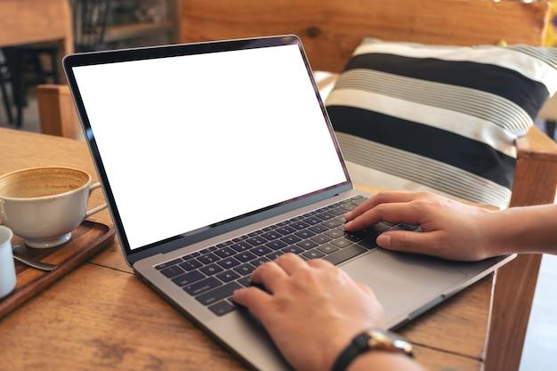 Handen gebruiken en typen op laptop met leeg wit bureaubladscherm met koffiekopje op houten tafel in café