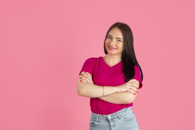 Handen gekruist. zwart-wit portret van jonge kaukasische brunette vrouw geïsoleerd op roze muur.