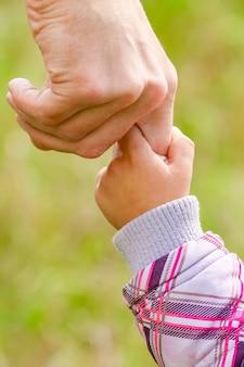 Handen gelukkige ouders en kind buiten in het park