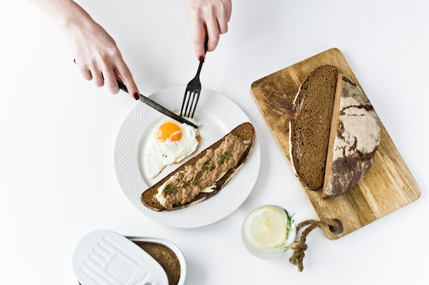 Handen gesneden met een mes en vork, gebakken ei, leverpastei op brood.