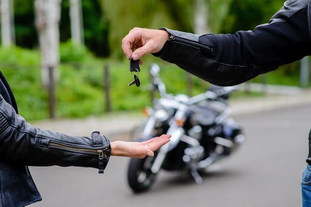 Handen geven de sleutels aan de motor door.