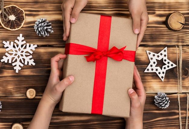 Handen geven of ontvangen van een geschenk in ambachtelijk papier met een rood lint op rustieke houten kerstmis en nieuwjaar achtergrond. bovenaanzicht