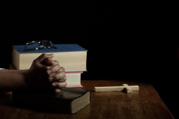 Handen gevouwen in gebed op een heilige bijbel in de kerk