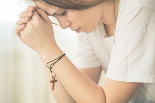 Handen gevouwen in gebed op een heilige bijbel in kerk concept voor geloof, spiritualiteit en religie, vrouw bidden op bijbel in de ochtend.