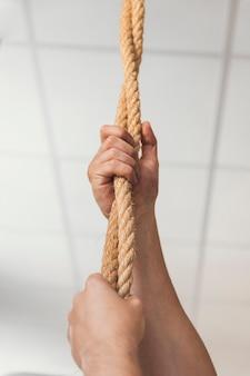 Handen grijpen touwen in de sportschool
