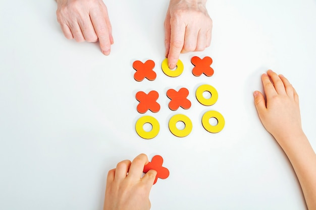 Handen grootmoeder en kleinzoon spelen tic-tac-toe houten bordspel