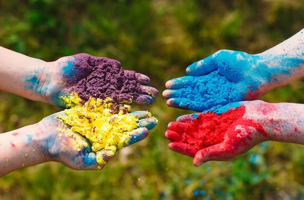 Handen / handpalmen van jonge mensen bedekt met paarse, gele, rode, blauwe geïsoleerde holi-festivalkleuren