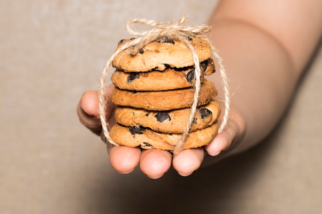 Handen houden chocoladekoekjes, chocoladekoekjes vastgebonden met een lint.