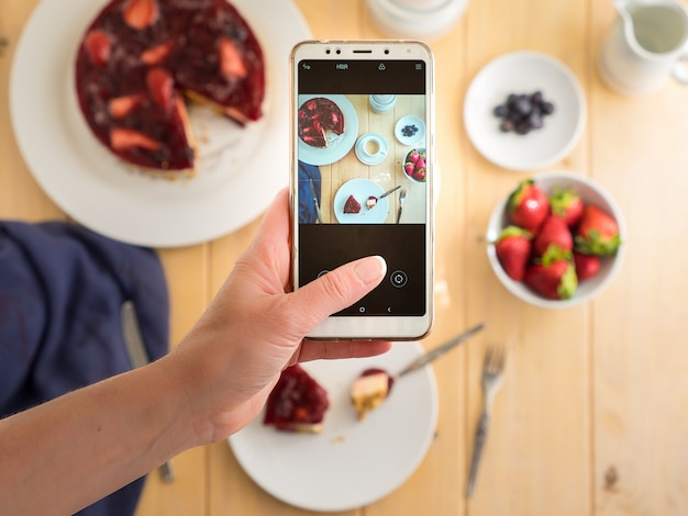Handen houden de telefoon, fotograferen kleurrijk, gezond voedsel op een lichte houten tafel. selectieve aandacht.