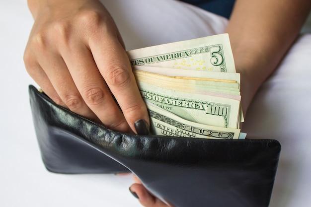 Handen houden dollarbiljetten en een kleine geldzak vast