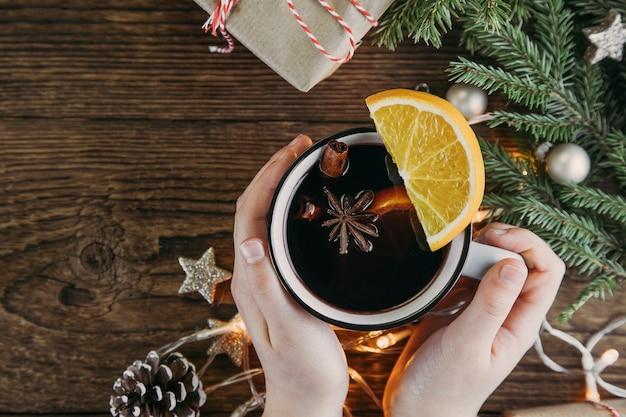Handen houden een beker met kerst- en nieuwjaarsdrank warme wijn, glühwein, punch of thee op een houten tafel naast een groene kerstboom en een slinger. plaats voor tekst.