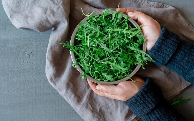 Handen houden een bord met verse groene rucola op een grijze achtergrond, concept tidewater green color.