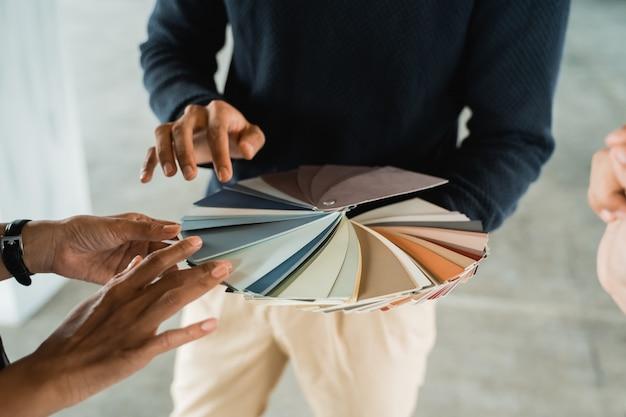 Handen houden een catalogus met verfmonsters voor aan klanten