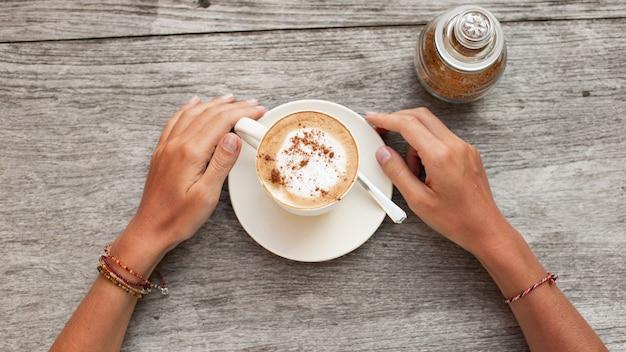 Handen houden een kopje koffie.