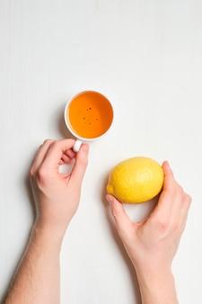 Handen houden een kopje thee met citroen verticaal.